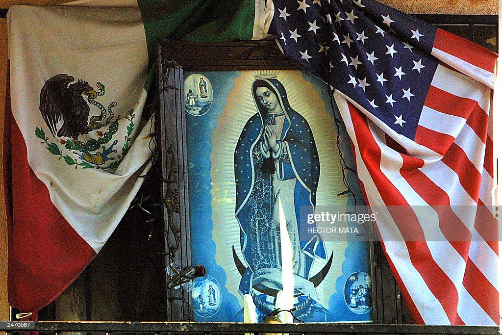 An image of the Virgen de Guadalupe sits alongside the US and Mexican flags at the entrance of a modest house in East Los Angeles 07 September 2003...
