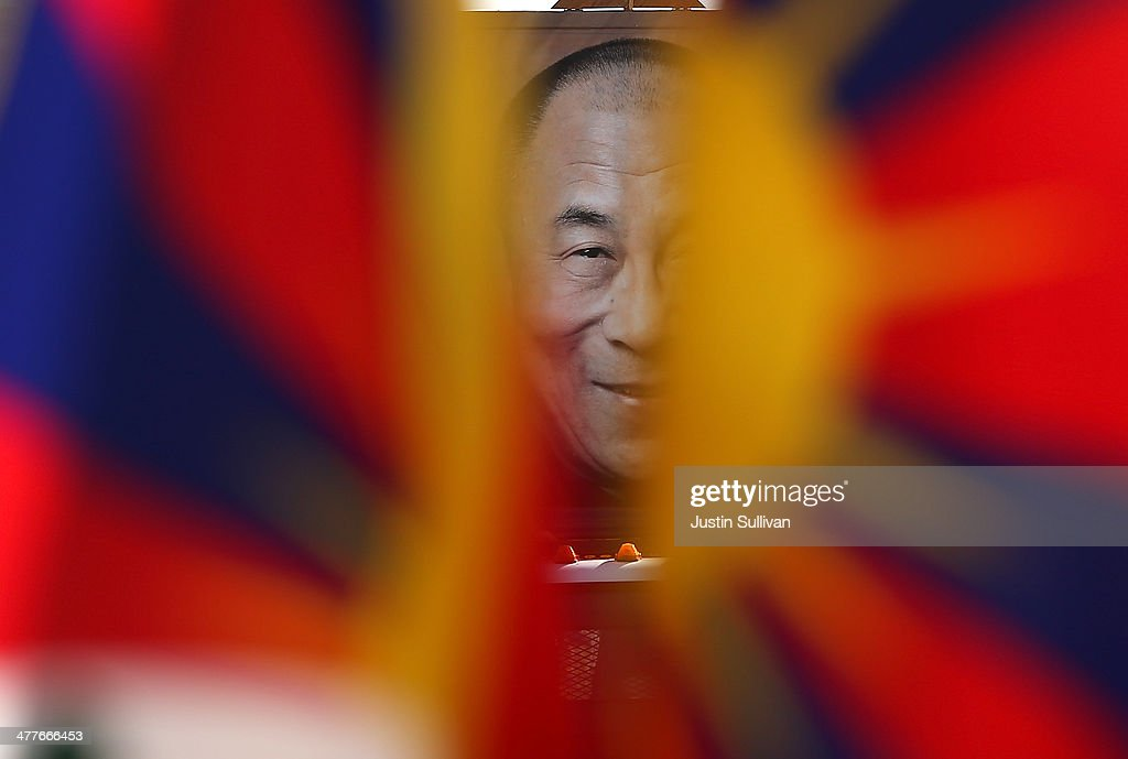 An image of Tibetan spiritual leader His Holiness the Dalai Lama is visible between Tibetan flags during a demonstration outside of San Francisco City Hall on March 10, 2014 in San Francisco, California. Hundreds of activists marked the 55th anniversary of the 1959 Tibetan uprising and the fifth anniversary of Tibetan self-immolation protests in Tibet.