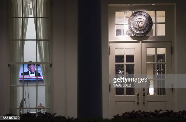 TOPSHOT An image of US President Donald Trump appears on a television screen inside the West Wing of the White House in Washington DC May 15 shortly...
