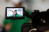 An image of US Team player Tiger Woods is seen on the viewfinder of a video camera as he is interviewed at a press conference during a practice round...