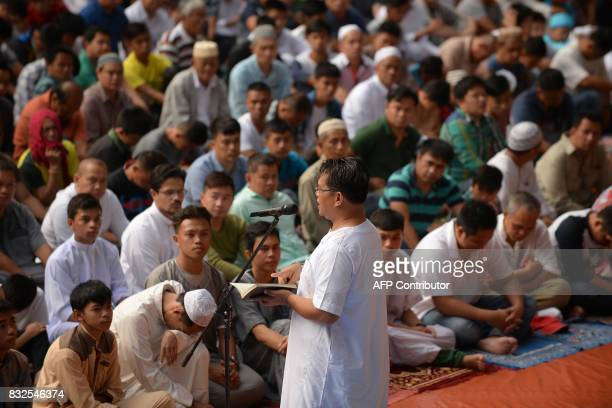 An imam delivers a sermon during an Eid alFitr prayer on the grounds of the city hall in Iligan City on the southern island of Mindanao on June 25...