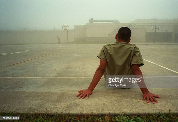 An immigrant boy sits in the fenced outdoor recreation area at Liberty County jail in Texas Children spend most of each day inside sterile windowless...