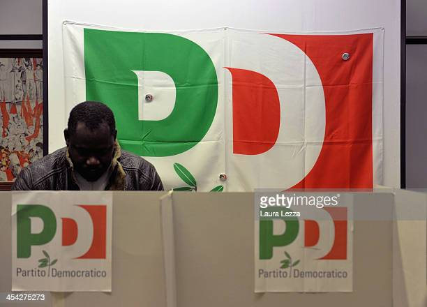 An immigrant casts his vote at a polling station during the PD primary elections on December 8 2013 in Livorno Italy Italians are voting today to...