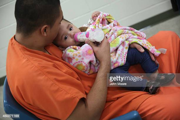 An immigrant detainee feeds his daughter during a family visitation visit at the Adelanto Detention Facility on November 15 2013 in Adelanto...