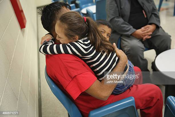 An immigrant detainee holds his children during a family visitation visit at the Adelanto Detention Facility on November 15 2013 in Adelanto...