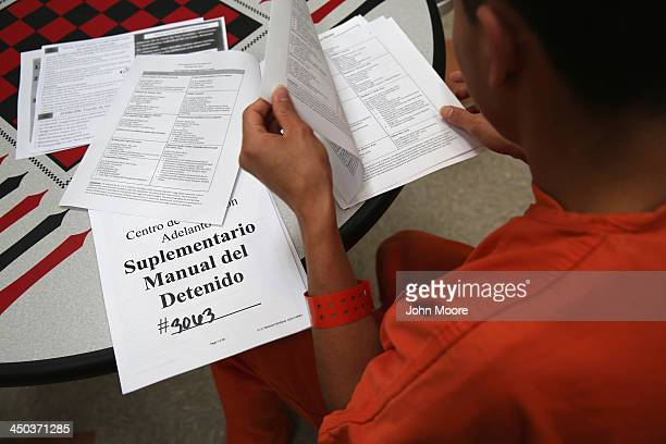 An immigrant detainee reads through paperwork in a general population block at the Adelanto Detention Facility on November 15 2013 in Adelanto...