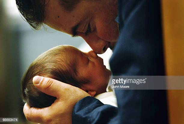 An immigrant from Mexico holds his son during a newborn care class at a community health center for lowincome patients on December 1 2009 in Aurora...