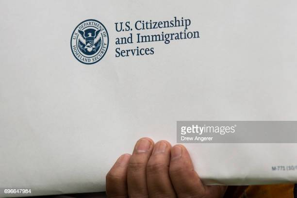 An immigrant holds a packet of citizenship information as he takes part in a naturalization ceremony at Franklin D Roosevelt Four Freedoms Park on...