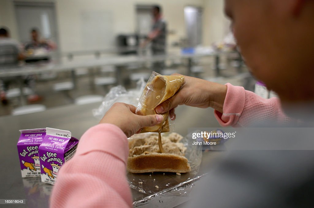 An immigrant inmate prepares breakfast at the Maricopa County Tent City jail on March 11, 2013 in Phoenix, Arizona. Peanut butter and jelly sandwiches are the standard daily breakfast at the facility. The tent jail, run by Maricopa County Sheriff Joe Arpaio, houses undocumented immigrants who are serving up to one year after being convicted of crime in the county. Although many of immigrants have lived in the U.S for years, often with families, most will be deported to Mexico after serving their sentences.