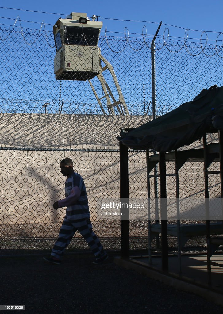 An immigrant inmate walks for excercise at the Maricopa County Tent City jail on March 11, 2013 in Phoenix, Arizona. The striped uniforms and pink undergarments are standard issue at the facility. The tent jail, run by Maricopa County Sheriff Joe Arpaio, houses undocumented immigrants who are serving up to one year after being convicted of crime in the county. Although many of immigrants have lived in the U.S for years, often with families, most will be deported to Mexico after serving their sentences.