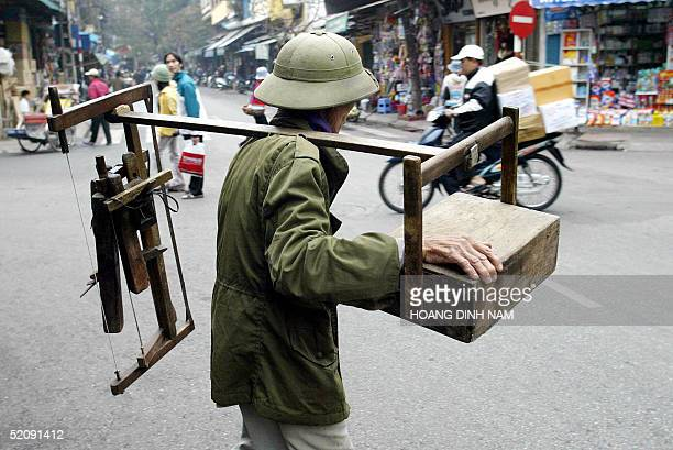 An immigrant laborer who works as street carpenter looks for customers along a street in Hanoi 01 February 2005 as Vietnamese prepare to celebrate...
