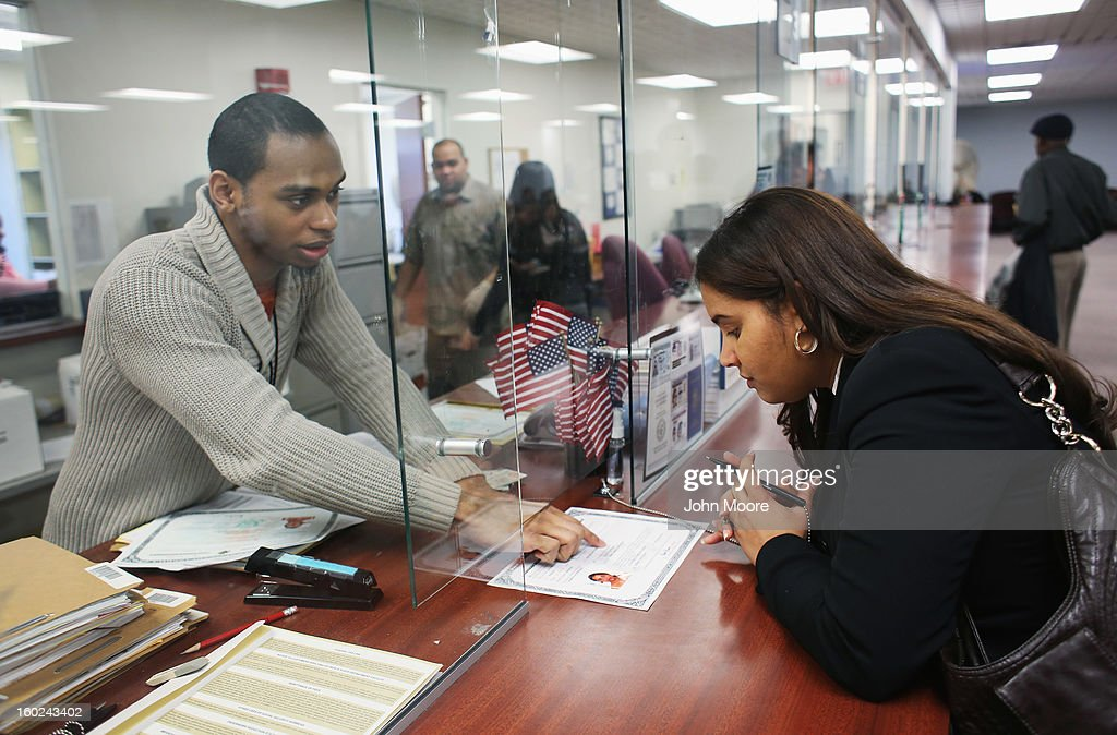 An immigrant prepares to sign a naturalization certificate before becoming an American citizen at the district office of U.S. Citizenship and Immigration Services (USCIS) on January 28, 2013 in Newark, New Jersey. Some 38,000 immigrants became U.S. citizens at the Newark office alone in 2012.
