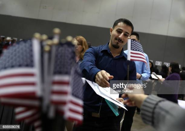 An immigrant receives an American flag as he prepares to be sworn in as US citizens during a naturalization ceremony held by US Citizenship and...