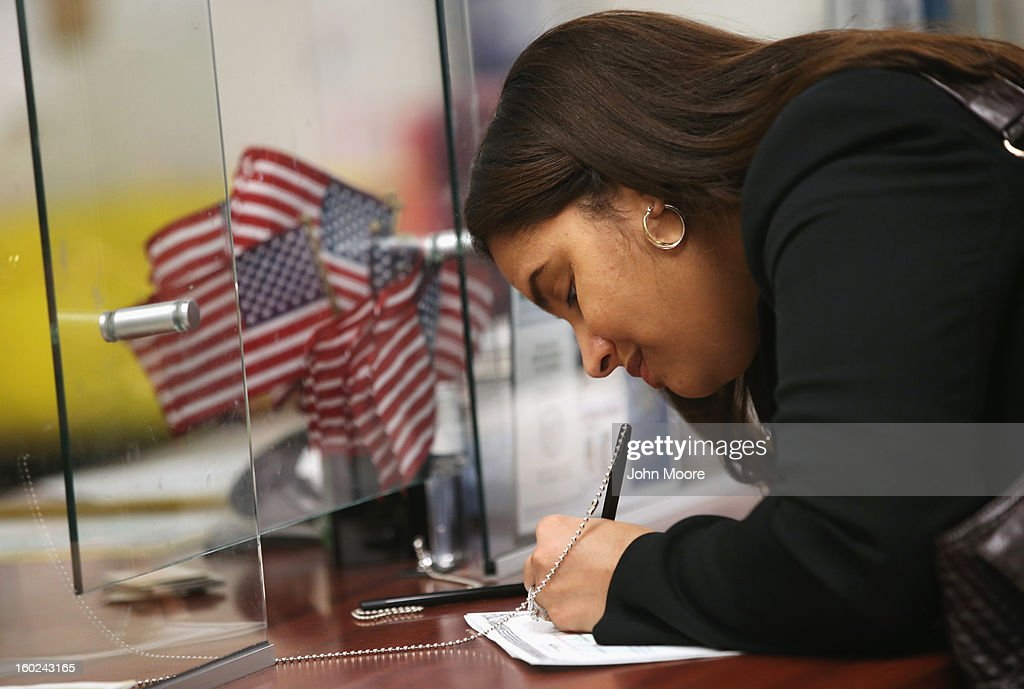 An immigrant signs a naturalization certificate before a ceremony to become a citizen at the district office of U.S. Citizenship and Immigration Services (USCIS) on January 28, 2013 in Newark, New Jersey. Some 38,000 immigrants became U.S. citizens at the Newark office alone in 2012.