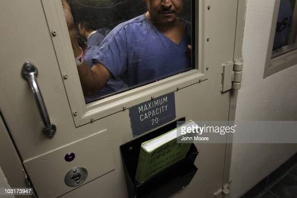 An immigrant stands in a holding cell at the US Immigration and Customs Enforcement detention facility for illegal immigrants on July 30 2010 in...