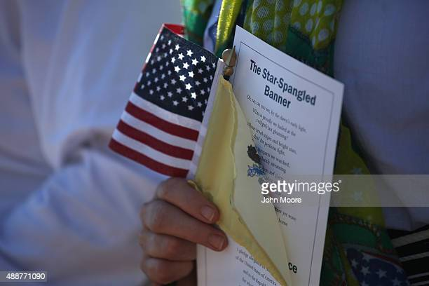 An immigrant takes part in a naturalization ceremony at Liberty State Park on September 17 2015 in Jersey City Pennsylvania One hundred immigrants...