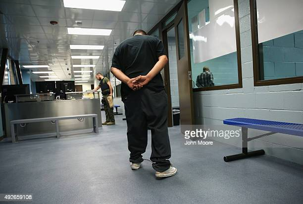 An immigrant walks in chains through a US Immigration and Customs Enforcement processing center after being detained on October 14 2015 in Camarillo...