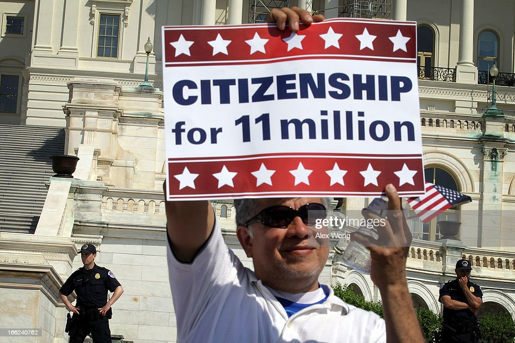An immigration activist holds up a sign on the West Lawn of the U.S. Capitol during an All In for Citizenship rally April 10, 2013 on Capitol Hill in Washington, DC. Tens of thousands of reform supporters gathered for the rally to call on Congress to act on proposals that would grant a path to citizenship for an estimated 11 million of the nation's illegal immigrants.