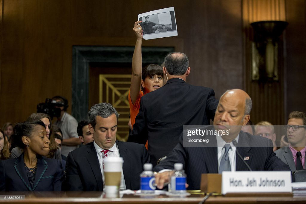 An immigration advocate disrupts a Senate Judiciary Committee hearing with <a gi-track='captionPersonalityLinkClicked' href=/galleries/search?phrase=Jeh+Johnson&family=editorial&specificpeople=5862084 ng-click='$event.stopPropagation()'>Jeh Johnson</a>, U.S. secretary of Homeland Security (DHS), right, in Washington, D.C., U.S., on Thursday, June 30, 2016. Johnson said gun control is a matter of homeland security during the hearing. Photographer: Andrew Harrer/Bloomberg via Getty Images