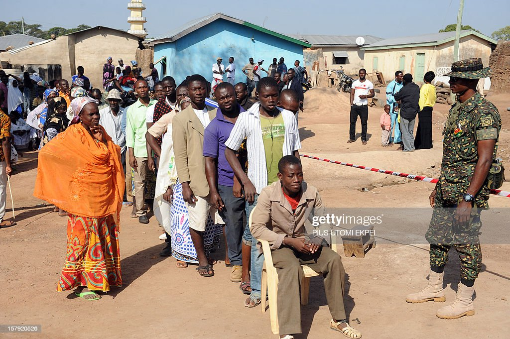An immigration officer stands in front of people queuing prior to vote at Bole polling station, northern Ghana, the native town of the presidential candidate for the ruling National Democratic Congress on December 7, 2012. Ghana voted in a high-stakes presidential election which is expected to be close, with the emerging country seeking to live up to its promise as a beacon of democracy in turbulent West Africa. AFP PHOTO/PIUS UTOMI EKPEI