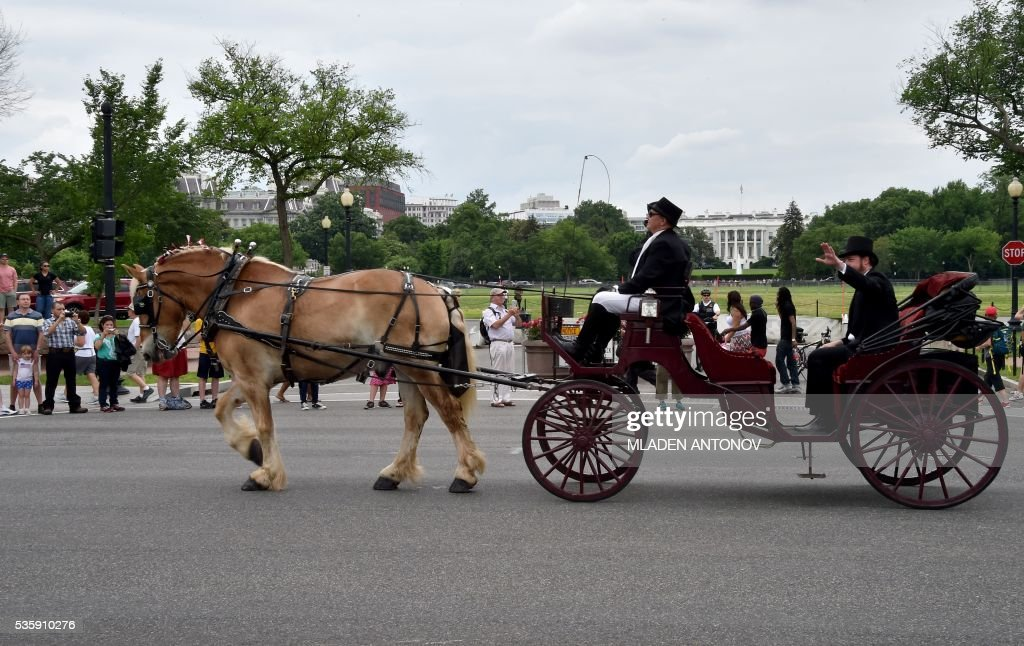 An impersonator of Abraham Lincoln rides a carriage in front of the White House during the Memorial Day Parade on Constitution Avenue in Washington DC on May 30, 2016. / AFP / MLADEN