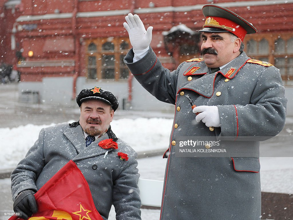 An impersonator of Soviet leader Josef Stalin waves while standing near an impersonator of Soviet leader Vladimir Lenin in central Moscow on March 5...
