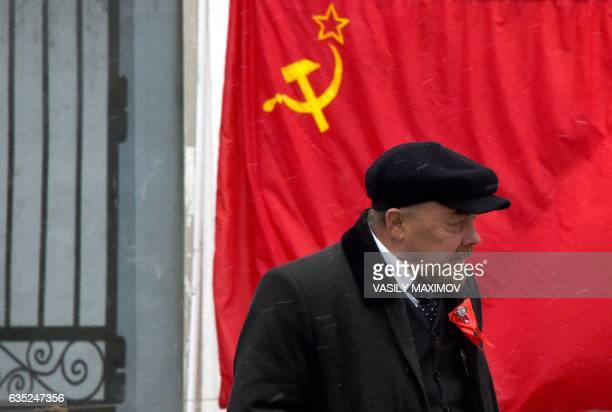 An impersonator of Soviet state founder Vladimir Lenin walks past a hammerandsickle red flag in central Moscow on February 14 2017 / AFP / Vasily...