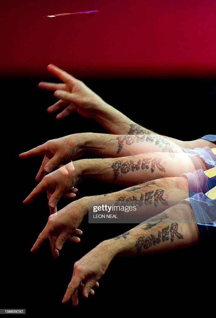 An in-camera multiple exposure composite of Phil Taylor of Britain as he takes part in the PDC World Championship darts final against Michael van Gerwen of the Netherlandsat Alexandra Palace in north London on January 1, 2013. AFP PHOTO/Leon Neal