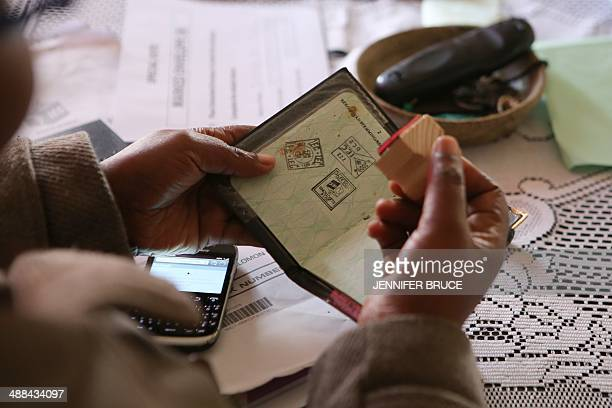An Independent Electoral official stamps a voters identity book during a special vote in Khayelitsha ahead of the general election tomorrow on May 6...