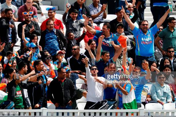 An India fan holds aloft the ball after he caught it following its rebound from the boundary marking following a hit for four runs during the ICC...