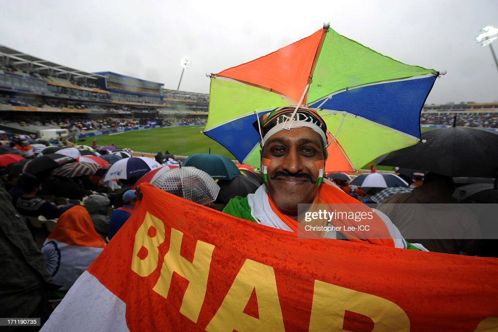 An India fan wearing a umbrella hat poses for the camera as the game is delayed due to rain during the ICC Champions Trophy Final match between England and India at Edgbaston on June 23, 2013 in Birmingham, England.