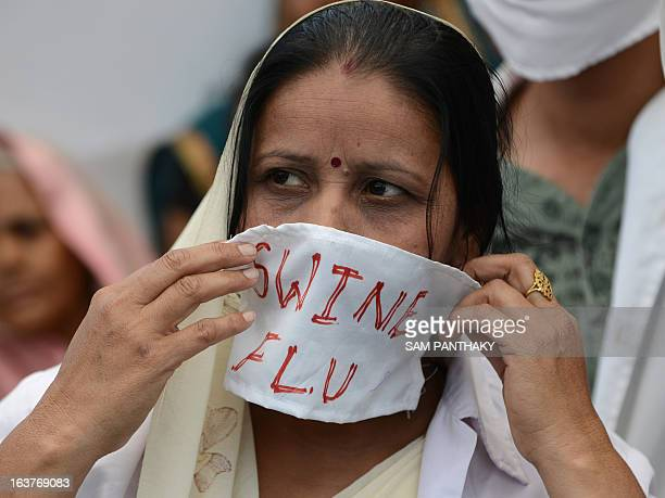 An Indian activist adjusts her face masks as other activists dressed as medical staff and patients perform a street play on the ongoing H1N1 swine...