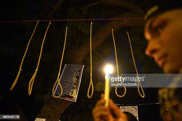 An Indian activist holds a candle near hangman's nooses during a candle light march to mark the second anniversary of the fatal gangrape of a student...