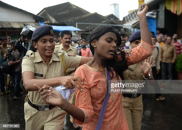 An Indian activist reacts as she gets detained by police as he tries to distribute pamphlets during a protest against the death sentence of Yakub...