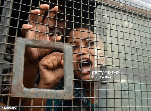 An Indian activist shouts slogans from inside a police van after getting detained during a protest against the death sentence of Yakub Memon a key...