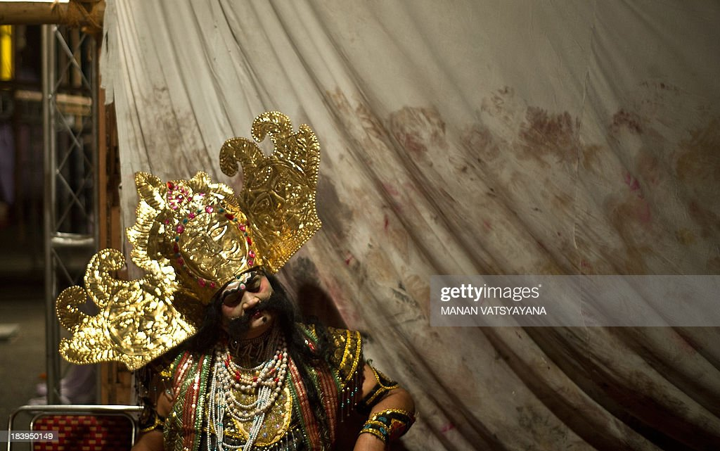 An Indian actor dressed as Demonking Ravana takes a break backstage for a Ramlila performance a dramatisation of Hindu God Rama's life in New Delhi...