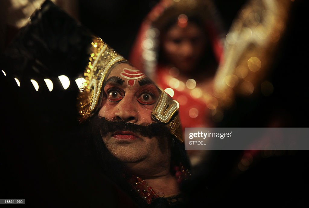 An Indian actor dressed as the Hindu demon king Ravan is reflected in a mirror as he prepares backstage for a performance of the Ramlila a...