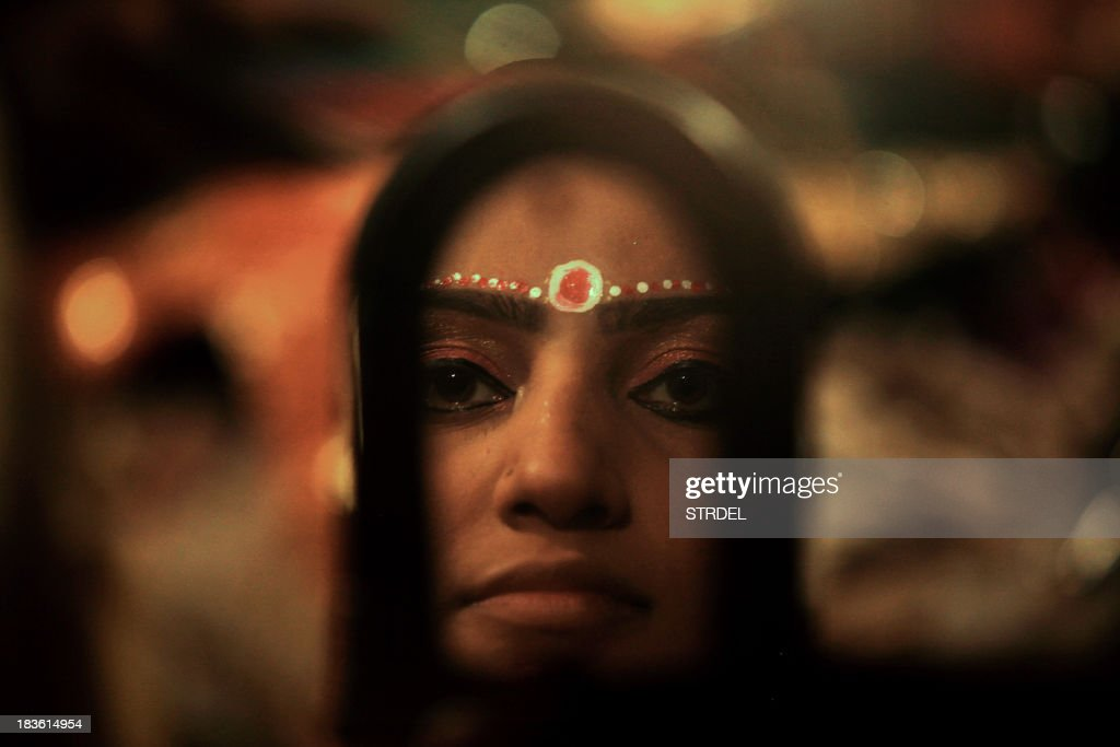 An Indian actor is reflected in a mirror as she prepares backstage for a performance of the Ramlila, a dramatisation of Hindu God Rama's life, in Jammu on October 7, 2013.Ramlila is a dramatic folk re-enactment of the life of Lord Rama's victory after a ten day battle with the ten headed Demon King Ravana, as described in the Hindu religious epic, the Ramayana.