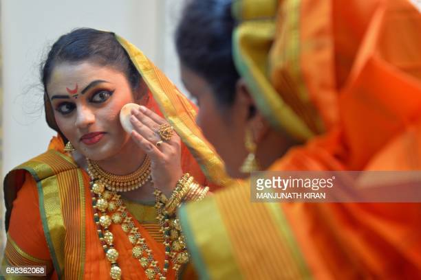 An Indian actor puts on makeup in the green room ahead of a stage performance in Bangalore on March 27 during World Theatre Day / AFP PHOTO /...