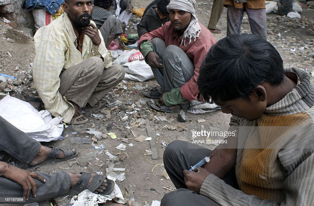 An Indian addict injects drugs in the old sector of New Delhi on November 29, 2012. Injecting drug users (IDU'Ss) are at high risk of contracting HIV/AIDS as blood transfer through the sharing of infected needles is an extremely effective way of transmitting HIV. AFP PHOTO/ Anna ZIEMINSKI