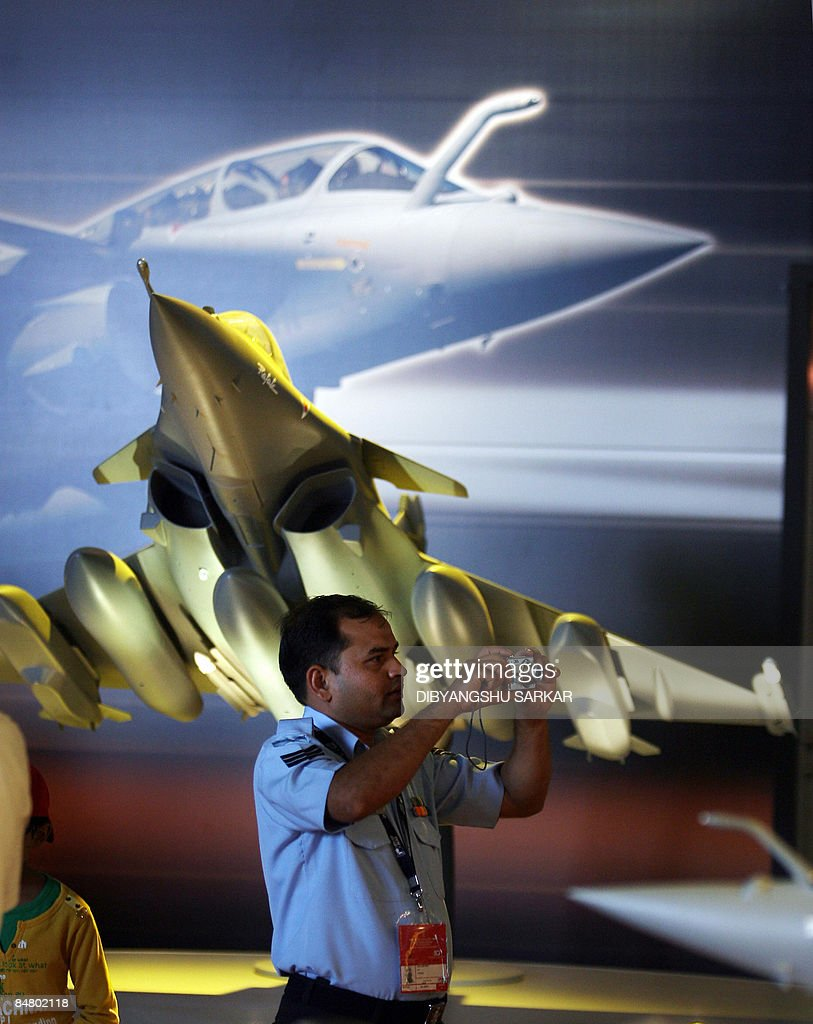 An Indian Air Force officer takes pictures as he stands beside a scale model of the French fighter aircraft Rafale, at the Yelahanka Air Force Station during the final day of the Aero India 2009 exhibition in Bangalore on February 15, 2009. South Asia's biggest airshow opened on February 11 with firms from 25 countries showcasing their latest hardware in a chase for multibillion-dollar contracts with the Indian military. AFP PHOTO/Dibyangshu SARKAR