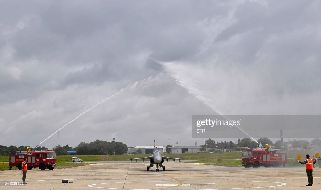 An Indian Air Force (IAF) pilot taxies a newly commissioned Tejas or Light Combat Aircraft (LCA) between welcoming waterspray from fire engines on a runway in Bangalore on July 1, 2016, during a ceremony in the southern Indian city. India's air force added its first domestically developed light fighter aircraft to its fleet, as it phases out ageing Russian jets dubbed 'Flying Coffins'. The bellow of conch shells and crack of breaking coconuts -- auspicious Hindu rituals -- sounded as the two Tejas jets were handed over to the Indian Air Force in the southern city of Bangalore. / AFP / STR