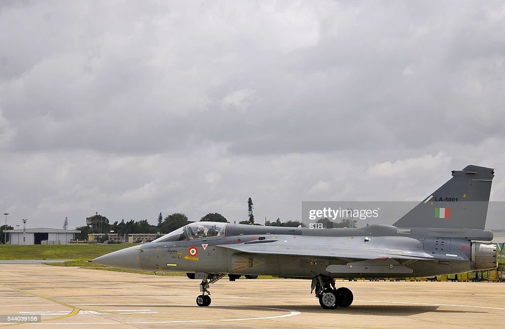 An Indian Air Force (IAF) pilot taxies a newly commissioned Tejas or Light Combat Aircraft (LCA) on a runway in Bangalore on July 1, 2016, during a ceremony in the southern Indian city. India's air force added its first domestically developed light fighter aircraft to its fleet, as it phases out ageing Russian jets dubbed 'Flying Coffins'. The bellow of conch shells and crack of breaking coconuts -- auspicious Hindu rituals -- sounded as the two Tejas jets were handed over to the Indian Air Force in the southern city of Bangalore. / AFP / STR