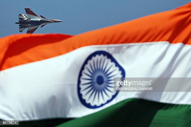 An Indian Air Force Sukhoi Su30 flies past an Indian national flag during the inauguration of Aero India 2009 at the Yelahanka Air Force Station in...