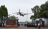 An Indian Airforce aircaft lands as Indian Airforce security personel stand guard outside Tambaram Airforce station in Chennai on July 23 2016 India...