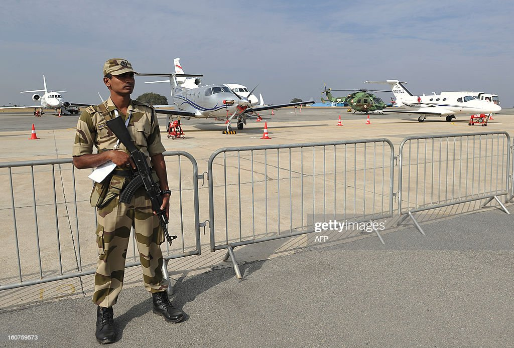 An Indian armed security personnel stands guard in front of aircraft on display for the 9th edition of Aero India 2013 at the Yelahanka Air Force station in Bangalore on February 5, 2013. The 5-day event starting from January 6 will be inaugurated by Indian defence minister AK Antony and is a major platform for foreign vendors. The biennial event is crucial to international participants and investors at a time when the Indian government is set to spend USD 100 billion in the defence sector within the next five years. AFP PHOTO/Manjunath KIRAN