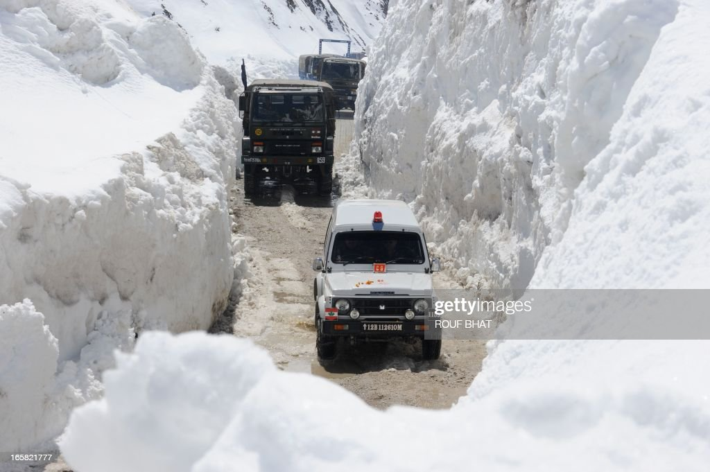 An Indian army convoy negotiates the Srinagar-Leh highway in Zojila Pass about 108 kms, 67 miles, east of Srinagar on April 6, 2013. The 443 km (275 mile) long highway was opened for the season by Indian Army authorities after the remaining snow at Zojila Pass, some 3,530 metres (11,581 feet) above sea level, had been cleared. The pass connects Kashmir with the Buddhist-dominated Ladakh region, a famous tourist destination known for its monasteries, landscapes and mountains. AFP PHOTO/ Rouf BHAT