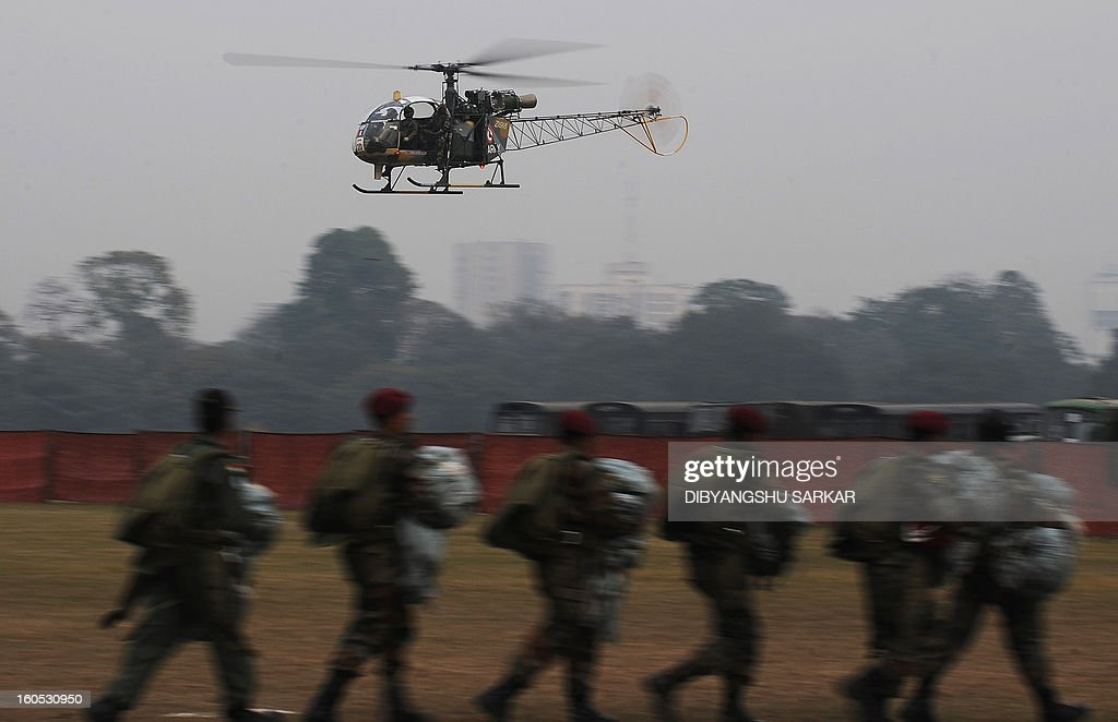 An Indian Army HAL Cheetah helicopter flies past as soldiers perform drills during an Army weaponry exhibition in Kolkata on February 2, 2013. The event was held as a recruitment tool for young Indians to join the country's armed forces. AFP PHOTO/Dibyangshu SARKAR