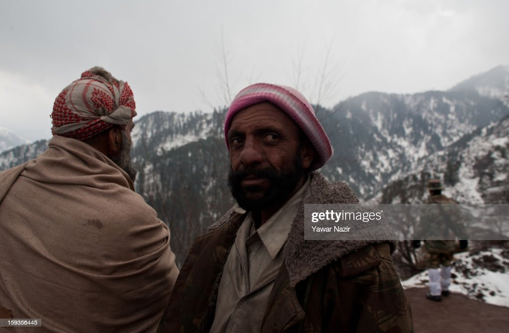 An Indian army officer stands guard as men look towards the snow covered mountains of Pakistan administered Kashmir Churunda village on January 12, 2013, northwest of Srinagar, the summer capital of Indian Administered Kashshmir, India. The village with a population of a little over 12,000 people has been bearing the brunt of cross-fire between nuclear rivals India and Pakistan. Last week a Pakistan solider was killed across the Line of Control (LOC), a military line that divides Indian-administered Kashmir from the Pakistan-administered Kashmir at this village. People living along the LoC have continually been at risk due to hostility between the armies of the two rival nations. Last year, in November, three people, including a pregnant woman, had died after a shell fired from Pakistan landed on one of the houses in the village. Tension between Pakistan and India has escalated after a fresh skimirish along the border. Both countries have summoned each other's envoy to protest against unacceptable and unprovoked' attacks.