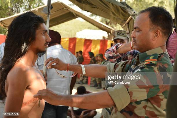 An Indian army officer takes physical measurements of a candidate during a physical fitness test at an Indian Army recruitment rally at Khasa some...